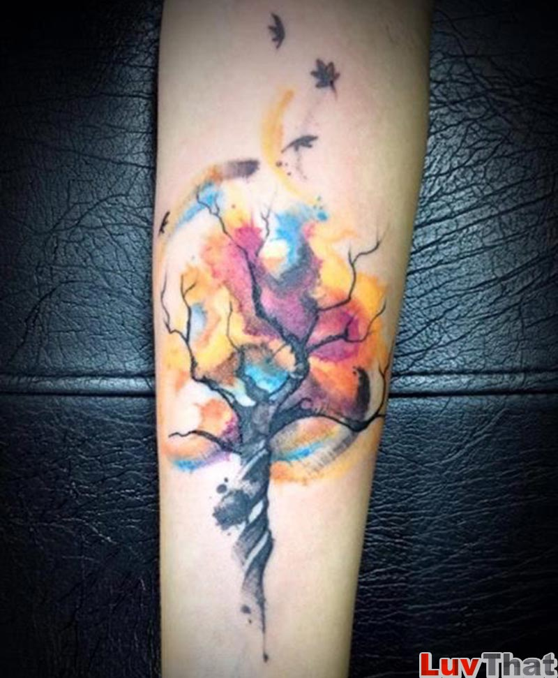 tree tattoo with colorful swirling watercolor leaves